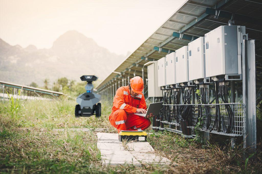 ingénieur ou électricien tenant un ordinateur portable pour l'inspection et la vérification avec le robot mobile GR100